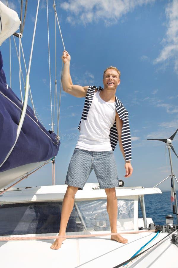 Blonder hübscher junger Mann auf Segelboot. lizenzfreie stockfotos