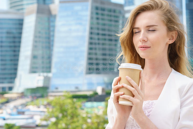 Blonder haltener Kaffee der Geschäftsfrau draußen auf Stadthintergrund stockfoto