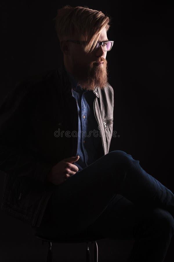 Blonder Hippie-Mann, der an auf einem Stuhl sitzt stockfotografie