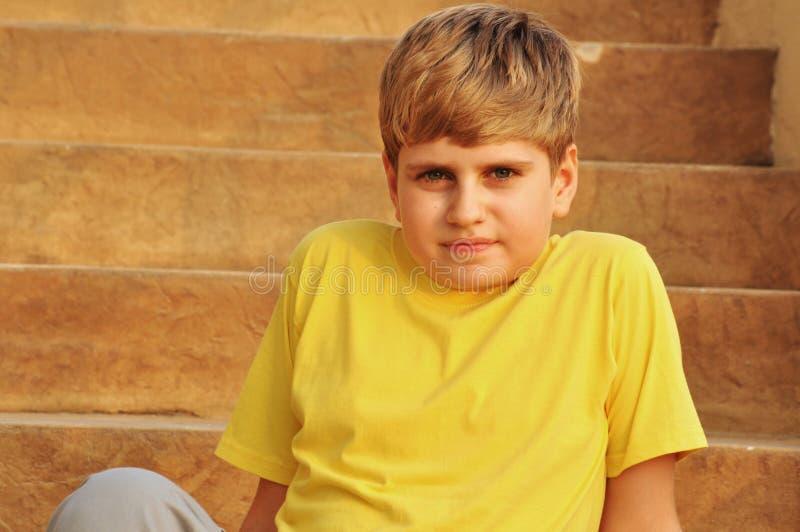 Blonder Junge, der auf Treppen am Sonnenuntergang sitzt lizenzfreies stockfoto