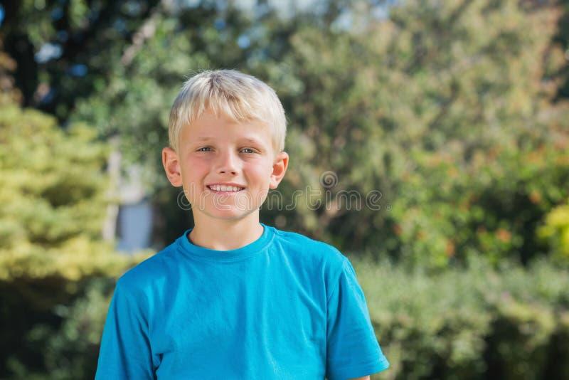 Blonder Junge, der an der Kamera lächelt lizenzfreie stockbilder