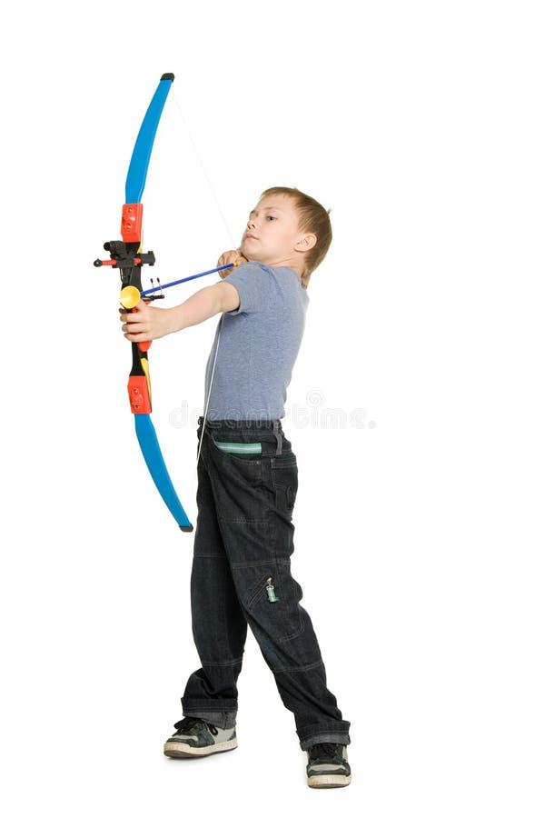 Blonder Junge, der einen Bogen schießt stockfoto