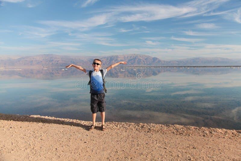 Blonder Junge, der hellen Tag auf schönem Salzufer des Toten Meers genießt israel stockbild