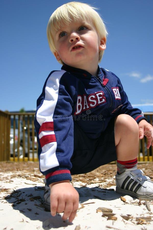 Blonder Junge, der im sandigen Spielplatz spielt stockbild