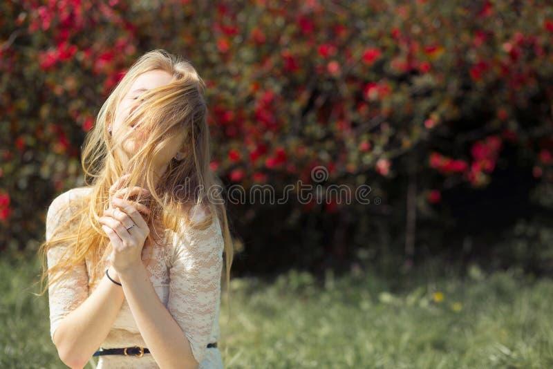 Blonder junge Frauen-im Frühjahr Garten Mädchen mit Fliegen-Haar-reizender lächelnder und genießender blühender Natur lizenzfreie stockbilder