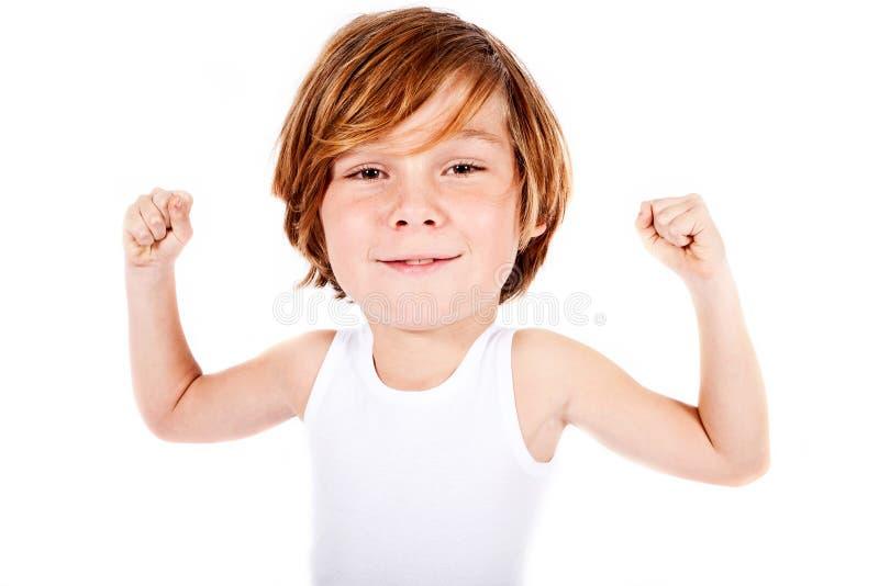 Blonder Junge mit dem Großkopf, der seine Muskeln biegt lizenzfreies stockbild