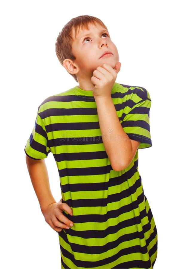 Blonder Kinderjunge im grünen T-Shirt denkt das Verkratzen stockfoto