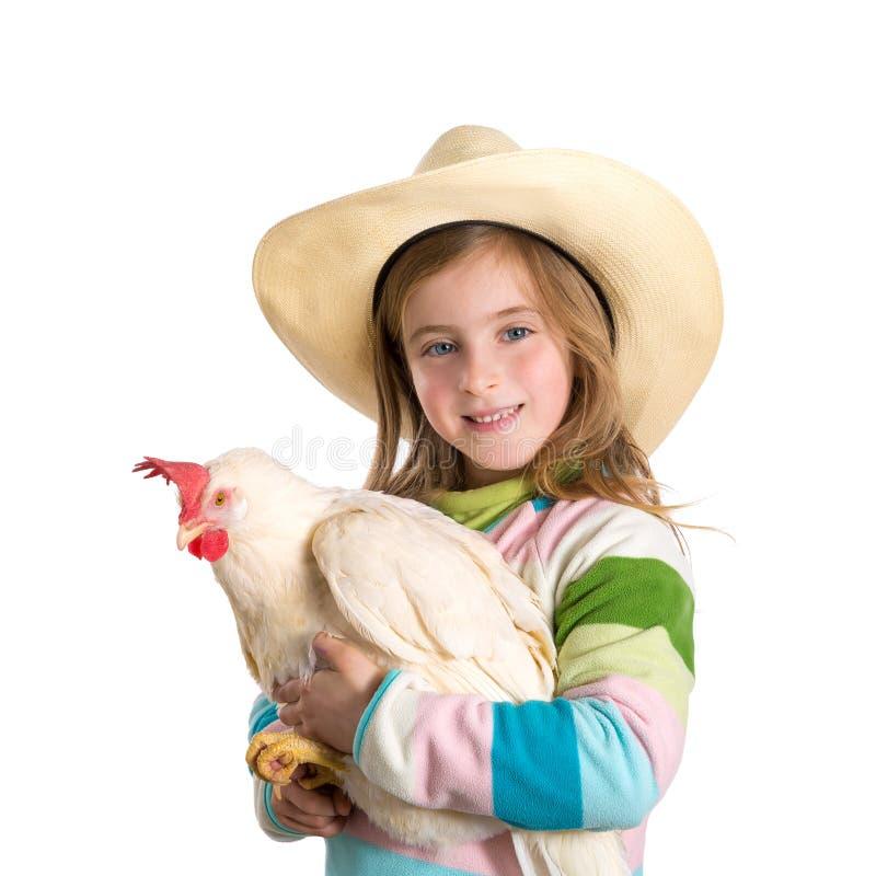 Blonder Kindermädchenlandwirt, der weiße Henne auf Armen hält lizenzfreies stockfoto