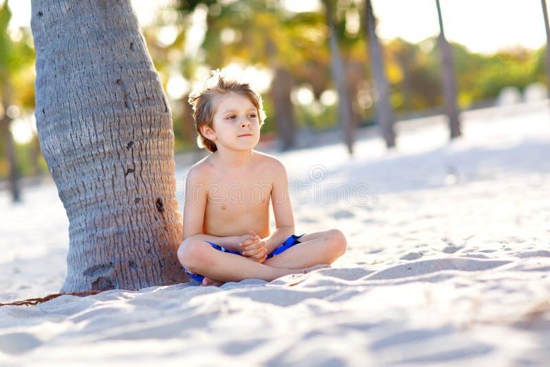 Blonder Kleinkindjunge, der Spaß auf Miami Beach, Key Biscayne hat Glückliches gesundes nettes Kind, das mit Sand und Betrieb spi stockbilder