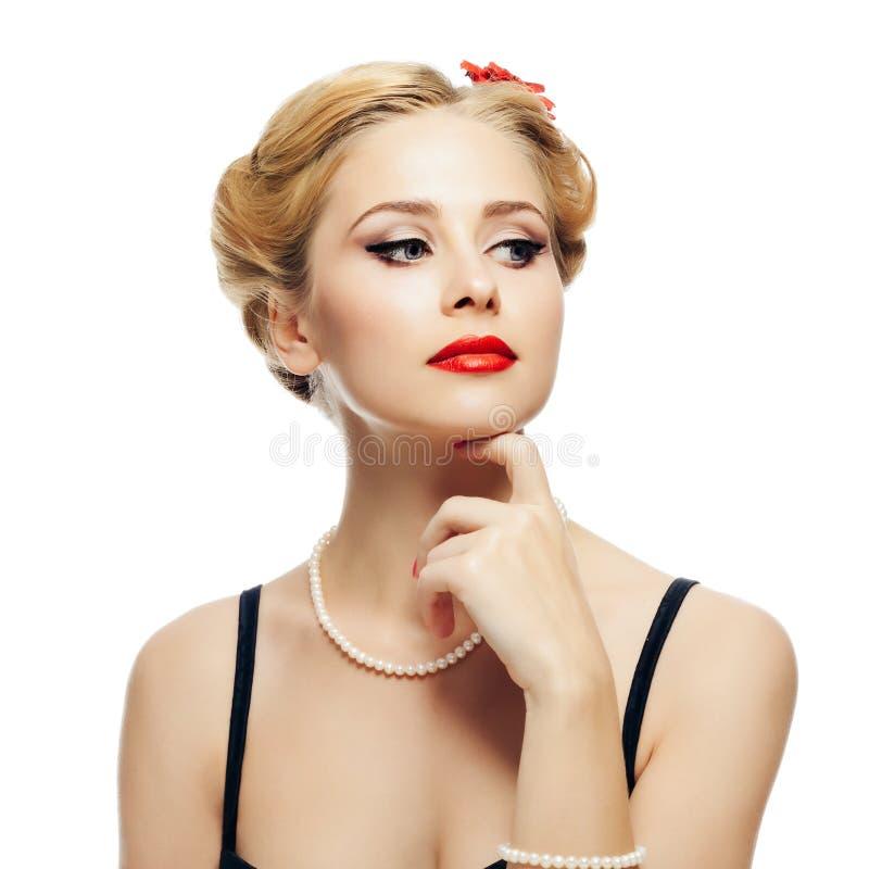 Blonder Mädchenartstift-oben in den schwarzen Kleider- und Perlenhalskettenblicken zur Seite und zum Notenkinn mit Ihrer Hand ein stockfotografie