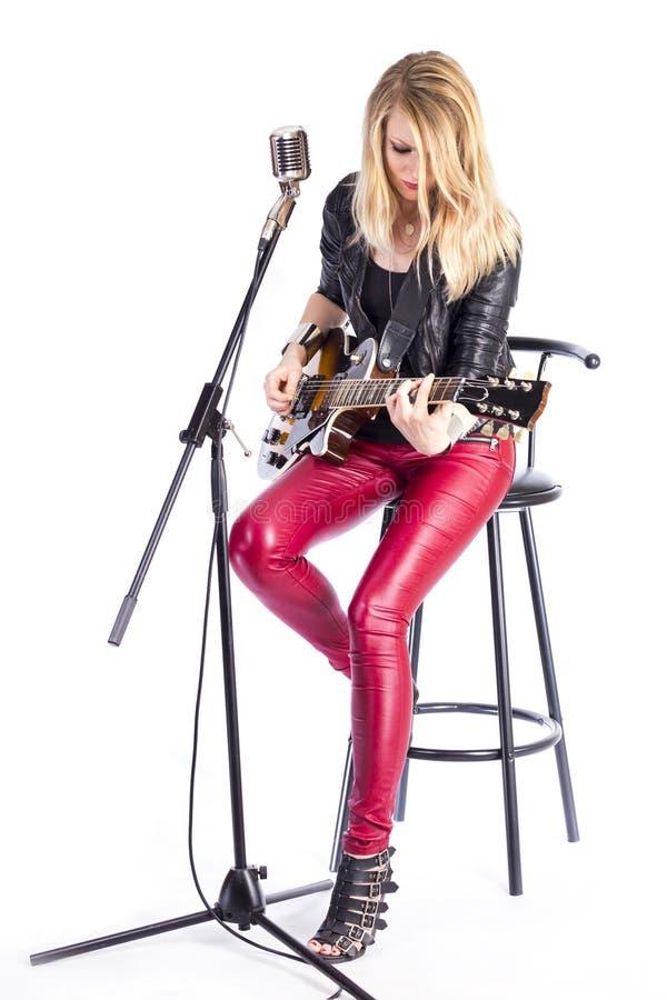 Blonder Mädchengitarrist mit E-Gitarre lernt Spiellied, sitzt auf Stuhl, singt in Retro- Mikrofon Lehrerin stockfoto
