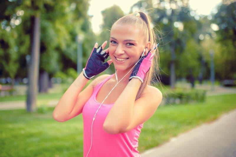 Blonder Musik hörender und ausarbeitender Athlet der glücklichen Eignung stockfotografie
