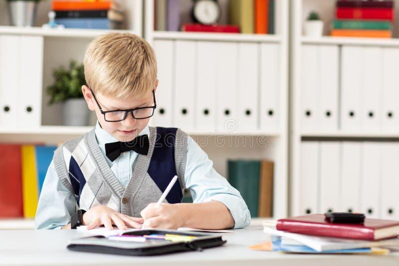 Blonder Schüler in einer Strickjacke, die eine Klassenarbeit tut stockfoto