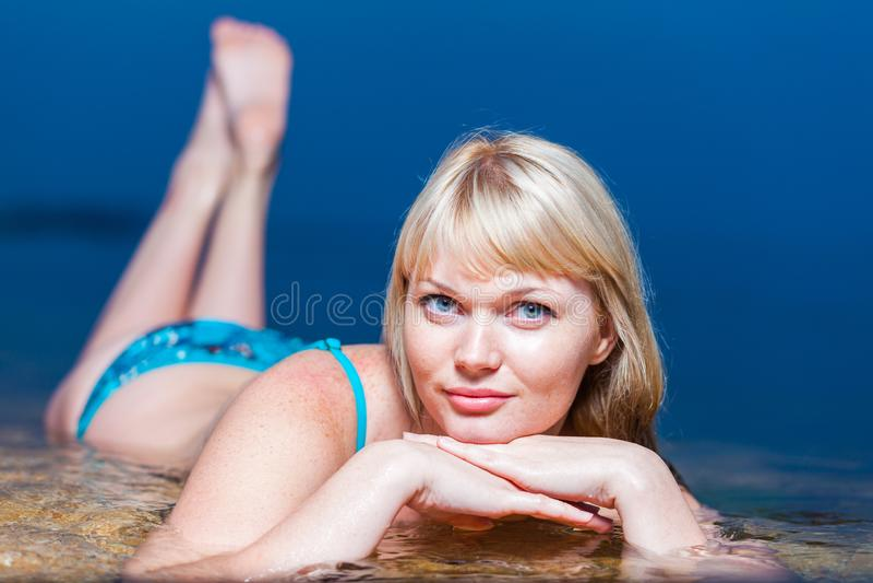 Blonder tragender Bikini der jungen Frau, liegend im Wasser lizenzfreie stockfotos