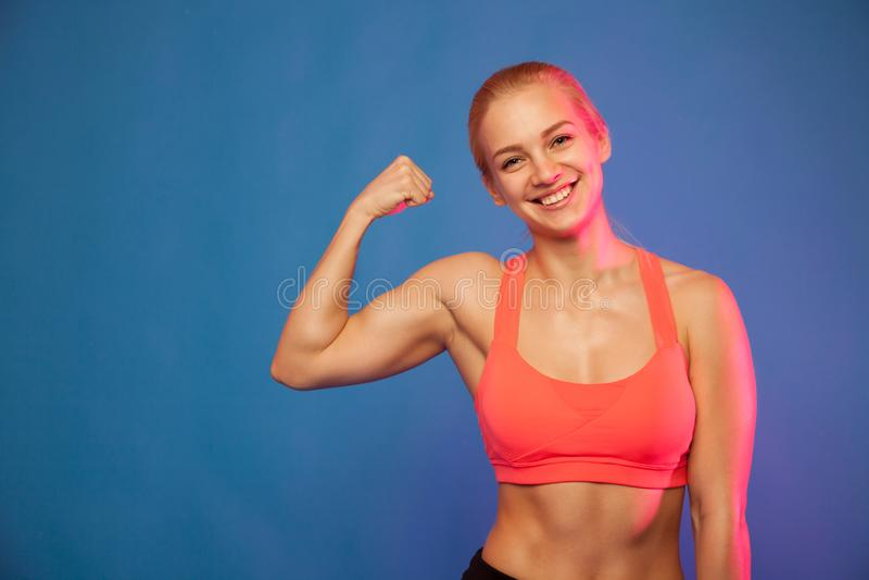 Blonder weiblicher Athlet, der Bizeps auf blauem Hintergrund zeigt, stockfotografie