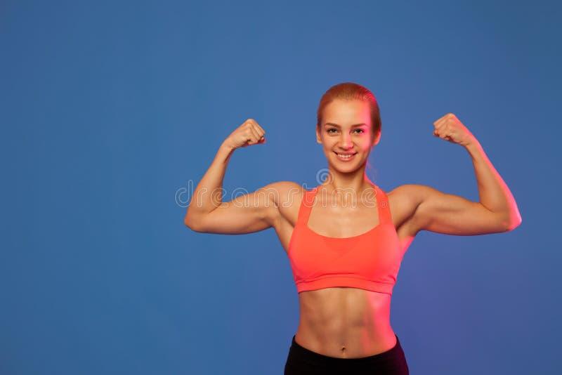 Blonder weiblicher Athlet, der Bizeps auf blauem Hintergrund zeigt, lizenzfreie stockfotografie