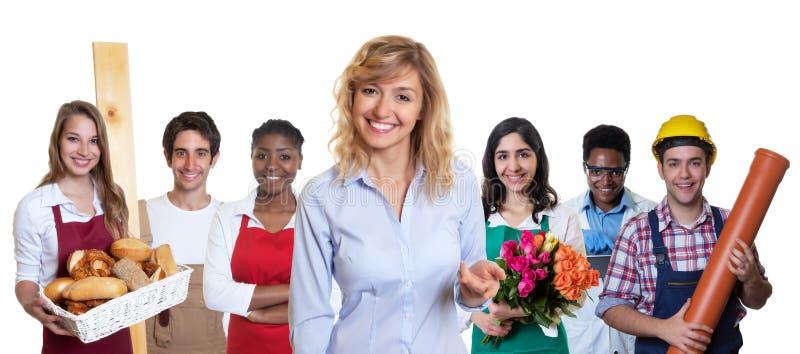 Blonder weiblicher Geschäftsauszubildender mit Gruppe anderer internationaler Lehrlinge lizenzfreies stockbild