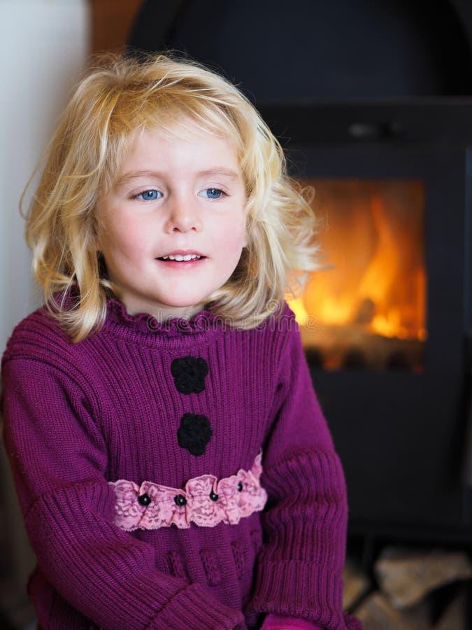 Blondes blauäugiges kleines Mädchen, das vor einem Kamin sitzt lizenzfreie stockfotos