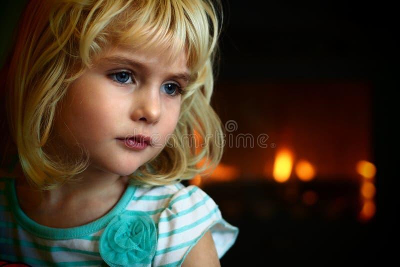 Blondes blauäugiges kleines Mädchen, das vor einem Kamin sitzt stockbild