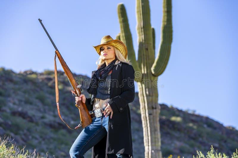 Blondes Cowgirl mit Waffen im amerikanischen Südwesten lizenzfreies stockfoto