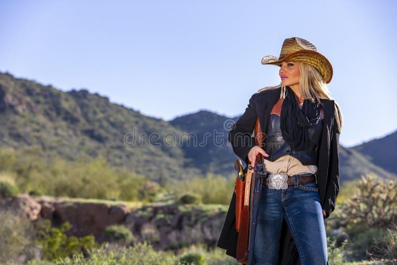 Blondes Cowgirl mit Waffen im amerikanischen Südwesten stockfotos
