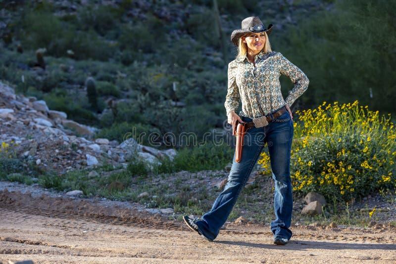 Blondes Cowgirl mit Waffen im amerikanischen Südwesten stockbild