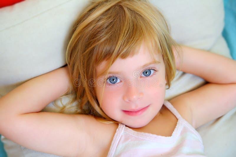 Blondes entspanntes Mädchen auf dem Lächeln der blauen Augen des Kissens stockfotos