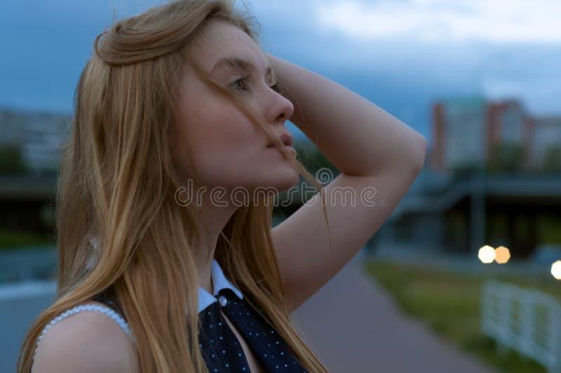 Blondes Frauenporträt auf Straße Mädchen, das oben bewölktem Himmel betrachtet A stockfotografie