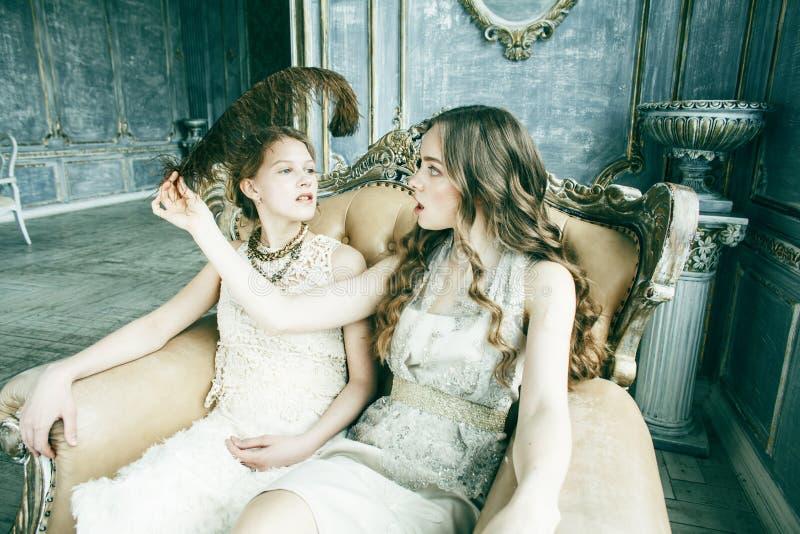 Blondes gelocktes Frisurm?dchen der h?bschen Zwillingsschwester zwei im Luxushausinnenraum zusammen, reiches Konzept der jungen L lizenzfreies stockfoto