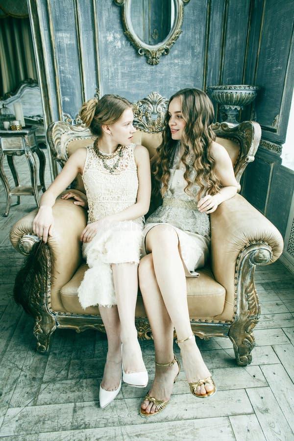 Blondes gelocktes Frisurm?dchen der h?bschen Zwillingsschwester zwei im Luxushausinnenraum zusammen, reiches Konzept der jungen L stockfotos