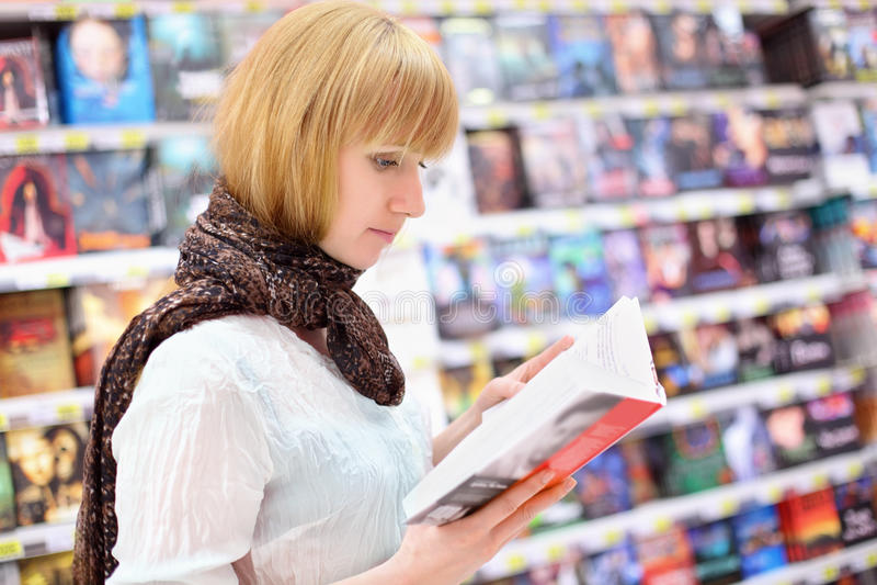Blondes girlreads Buch im Supermarkt stockbilder