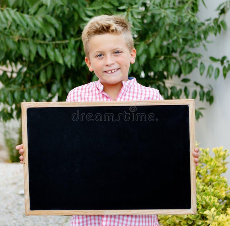 Blondes Kind, das einen Schiefer hält lizenzfreies stockbild