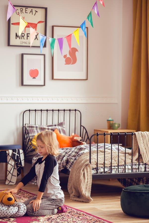 Blondes Kind, das mit Spielwaren in Weinlese angeredetem Unisexschlafzimmer spielt lizenzfreies stockbild