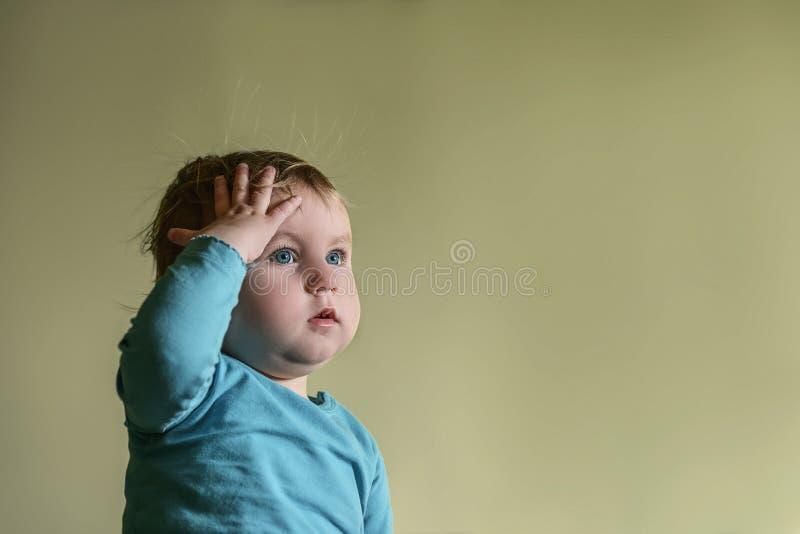 Blondes Kind mit blauen Augen hält eine Hand auf seinem Kopf zum Som stockfoto