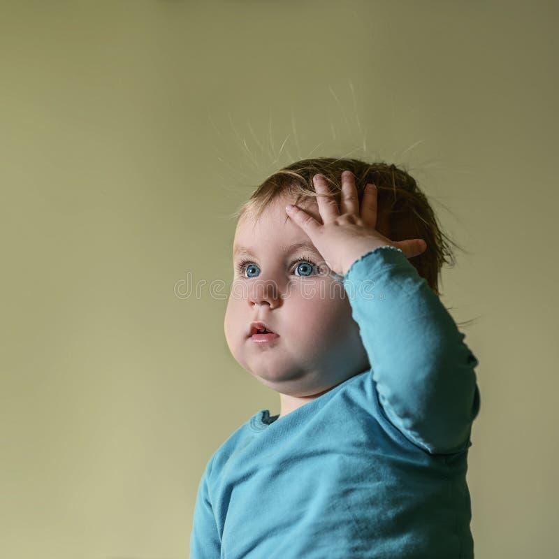 Blondes Kind mit blauen Augen hält eine Hand auf seinem Kopf zum Som stockbild
