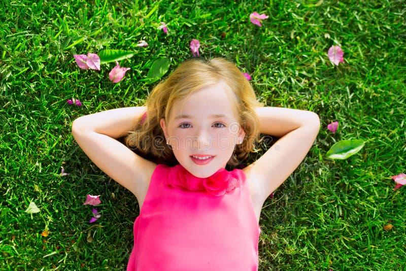Blondes Kindermädchen, das auf lächelnder Luftaufnahme des Gartengrases liegt lizenzfreies stockfoto