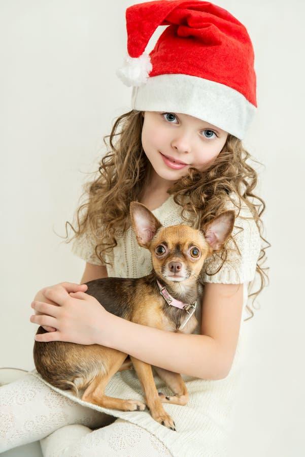 Blondes Kindermädchen in Santa Claus-Hut mit kleinem Schoßhund lizenzfreie stockfotos