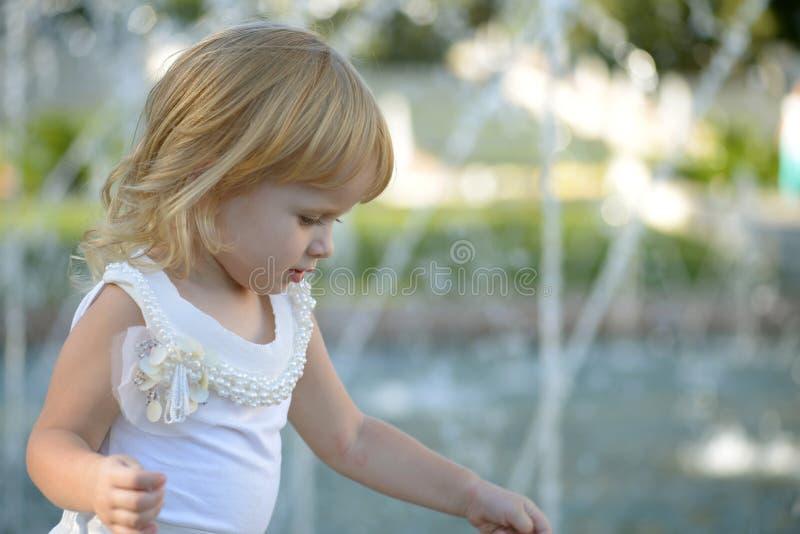 Blondes kleines Mädchen in einem Park nahe dem Brunnen lizenzfreie stockfotos