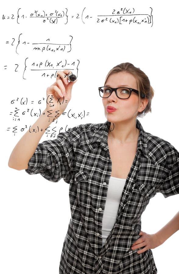 Blondes Kursteilnehmermädchen, das eine mathematische Formel zeichnet stockfotografie