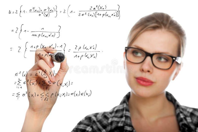 Blondes Kursteilnehmermädchen, das eine mathematische Formel zeichnet stockfoto