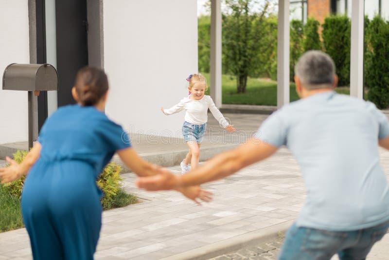 Blondes lächelndes Mädchen beim Laufen zu ihren Eltern lizenzfreie stockfotos