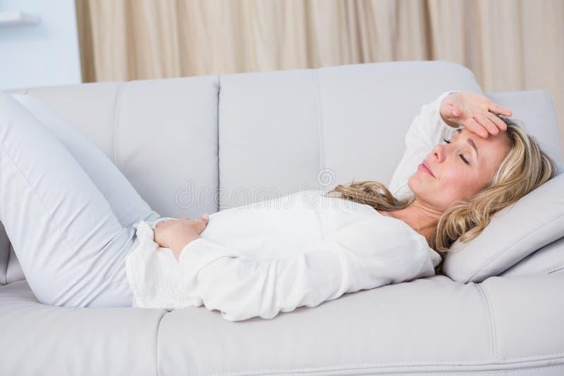 Blondes Lügen auf der Couch, die Magen und Hauptschmerz erhält stockbild