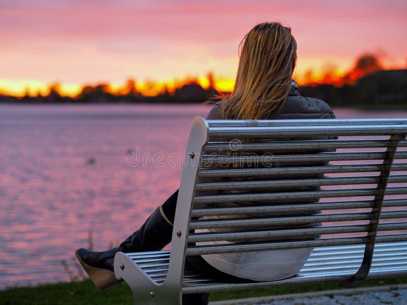 Blondes Mädchen auf Bank Sonnenuntergang genießend stockfotografie