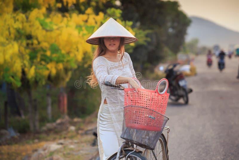 blondes Mädchen auf Vietnamesisch kleiden und Hut nahe Fahrrad auf Straße an stockbild