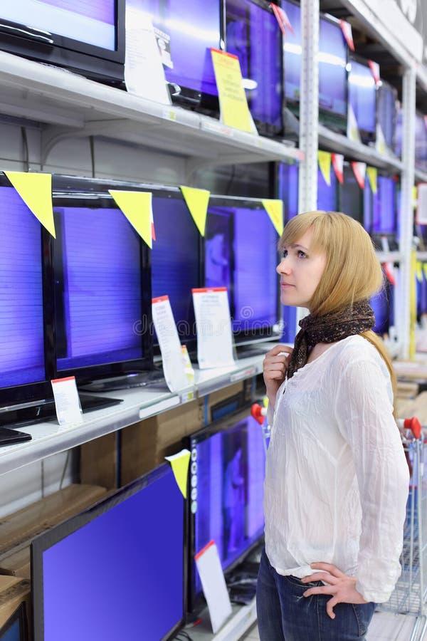 Blondes Mädchen betrachtet Plasma Fernsehapparate im Supermarkt lizenzfreie stockfotos