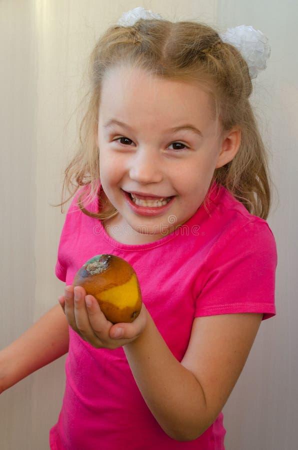 Blondes Mädchen bietet mit einem Schmunzeln eine faule Birne an stockfotografie