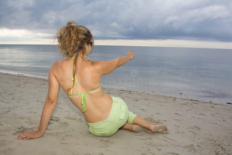 Blondes Mädchen, das auf das Meer auf Sonnenuntergang zeigt stockbilder