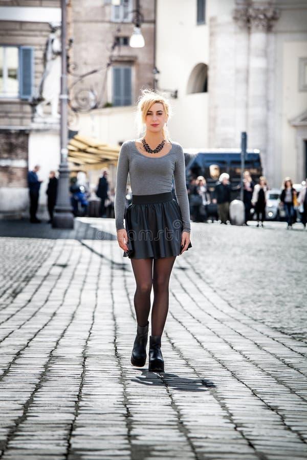 Blondes Mädchen, das auf die Straße in der Stadt trägt einen Rock geht lizenzfreies stockbild