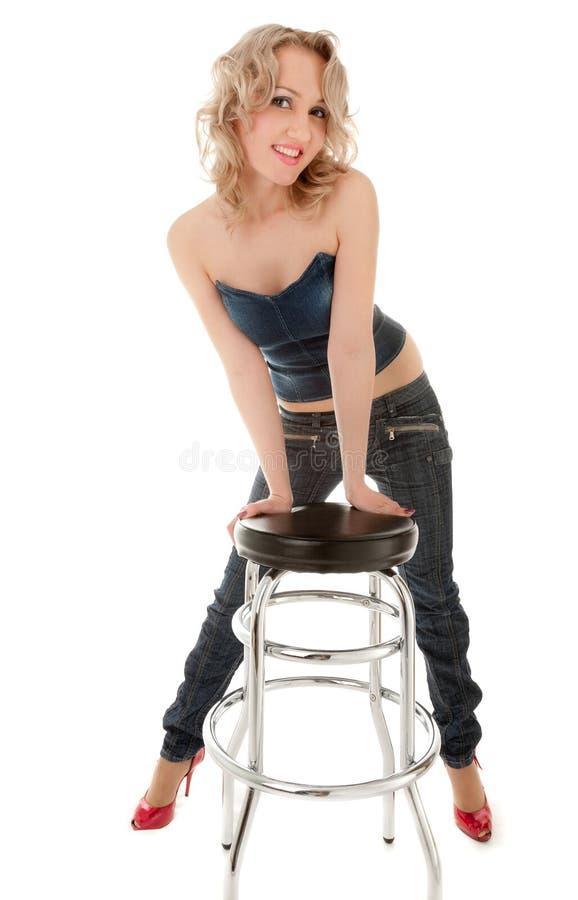 Blondes Mädchen, das auf einem Stabstuhl sich lehnt lizenzfreies stockbild
