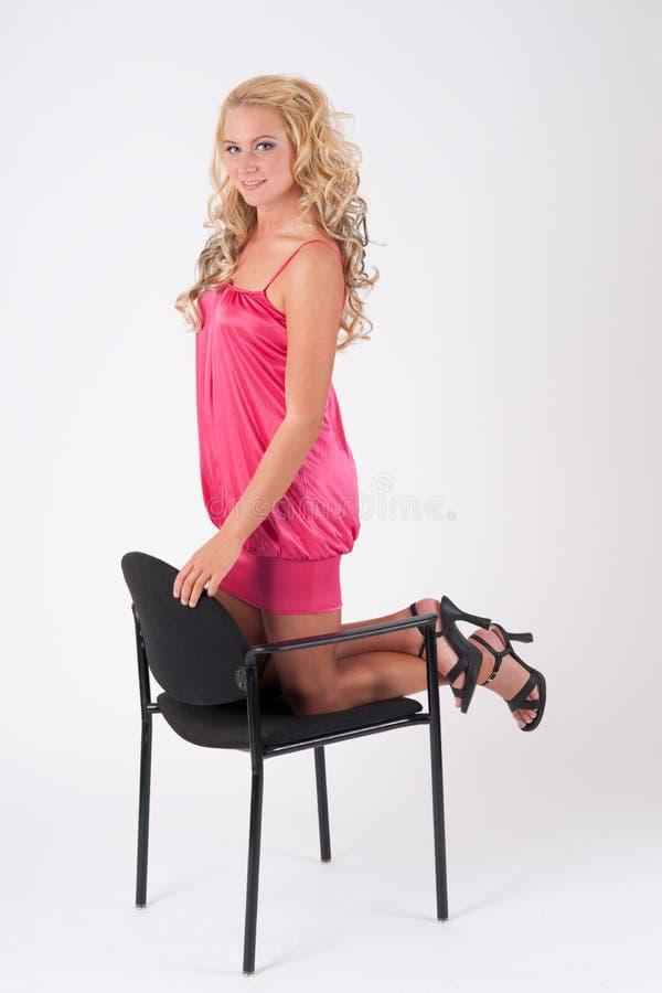 Blondes Mädchen, das auf einem Stuhl sich lehnt stockfotografie